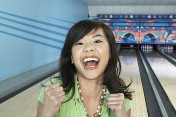 young woman at bowling alley celebrating portrait