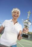 smiling senior woman holding tennis trophy on tennis court