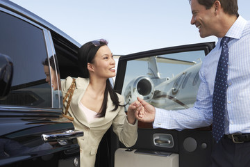 businessman helping woman get out of car parked near private jet side view