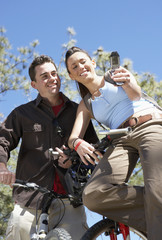 couple on mountain bikes using mobile phone photographing selves low angle view.