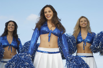 cheerleaders in costume with pom poms