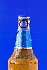 bottle of beer isolated on blue background