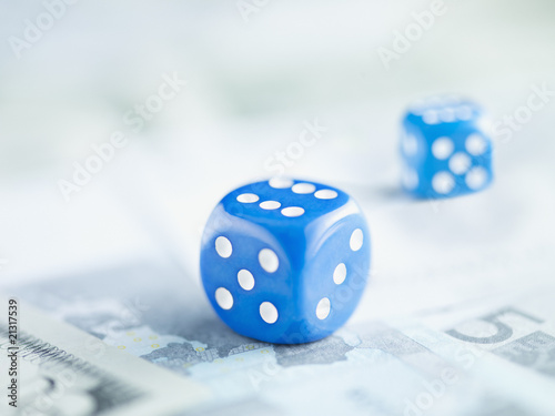 Two blue dice on pile of euro notes