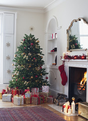 Christmas tree surrounded with gifts near fireplace