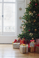 Christmas gifts beneath tree near window