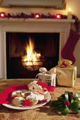 Christmas gifts and cookies near fireplace