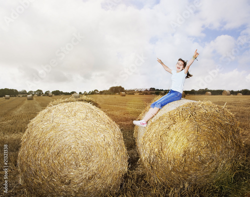 Girl with arms raised sitting on bale of hay