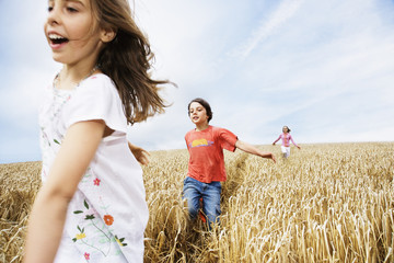 Children running in wheat field
