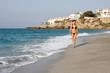 Beautiful young woman walking on the beach