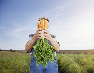 Farmer hiding face behind carrots