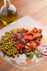 dish with octopus in tomato sauce and peas