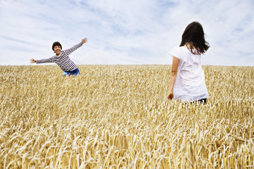 Boy and girl playing in wheat field