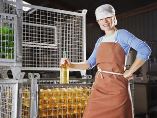 Woman posing in front of bins of bottles