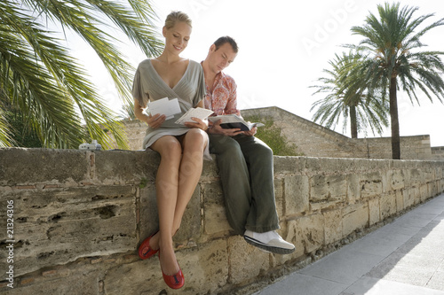 Man and woman sitting and reading on wall