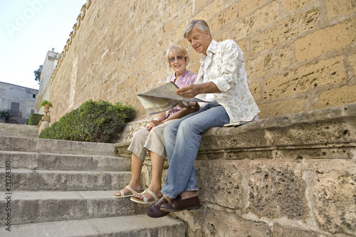 Man and woman sitting and reading map