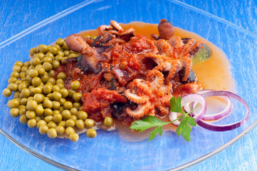 dish with octopus with tomato sauce and peas