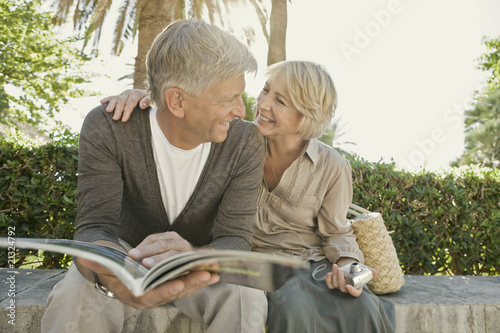 Man and woman sitting on wall with guidebook