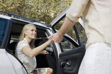 Man helping woman  exit car