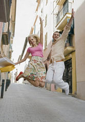 Man and woman jumping in street