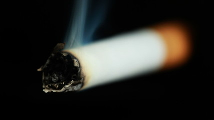 Smoldering Cigarette closeup, isolated on black