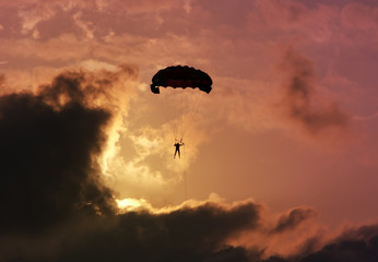 Parachutist against a colorful sunset and clouds.