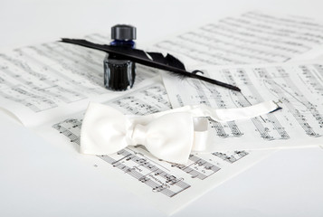 Ink bottle, feather, bow-tie and notes