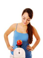 Woman weighing apple on kitchen scales