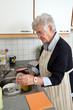 Seniorin beim Abwasch ihres Geschirrs