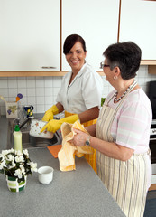 Pflegerin mit Seniorin beim Abwasch