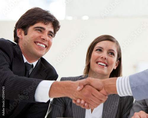 Smiling businessman and his colleague closing a deal with a part
