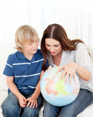 Interested child looking at a terrestrial globe with his mother