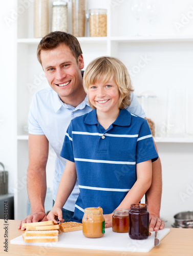 Smiling father helping his son prepare the breakfast