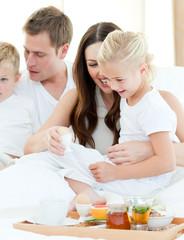 Elated family having breakfast sitting on bed
