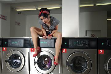 Sexy Frau im Waschsalon sitzt auf Waschmaschine