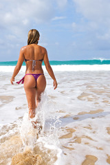 bikini girl walking towards the ocean and the waves beach