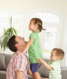 Daddy playing with kids at home poster