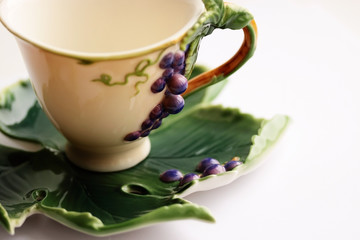 Porcelain tea cup and saucer with grapes ornament