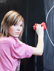 pretty young college student erasing the chalkboard/blackboard i