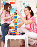 Child with  construction set lego in play room. poster
