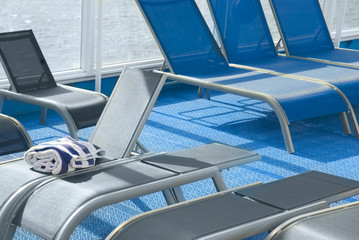 Blue and gray lounge chairs on deck of cruise ship