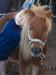 bambina che abbraccia un pony