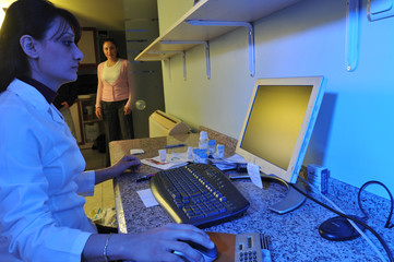 A laboratory assistant working at computer doctor looking