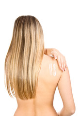 Causasian blonde woman creaming her back