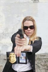A sexy FBI agent aiming a pistol.