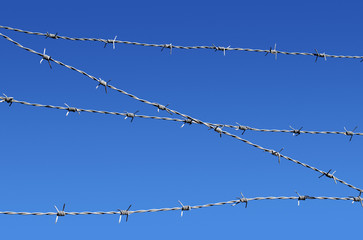 Barbed wire security fence close up and blue sky.