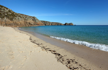 Porthcurno sandy beach shore line and Logan rock in Cornwall UK.