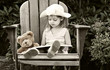Vintage style image of a child reading to her teddy bear.