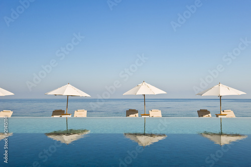 Deck chair and umbrella next to infinity pool