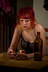 Young woman with near enpty bottle of wine