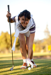 Woman placing a golf ball